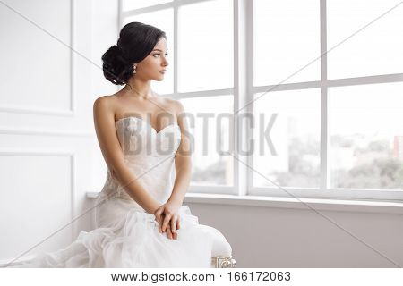 Bride in beautiful dress sitting on chair indoors in white studio interior like at home. Trendy wedding style shot. Young attractive multi-racial Asian Caucasian model like a bride against big window tender looking away. Side view