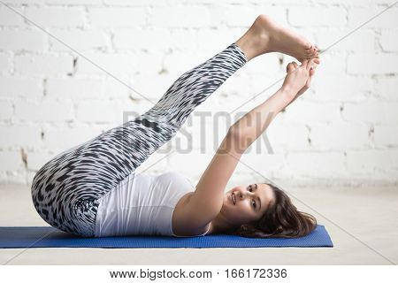Portrait of smiling beautiful young model working out in loft interior, doing stretching warmup, yoga exercise on mat, supta paschimottanasana. Sport active lifestyle concept. Full length, side view
