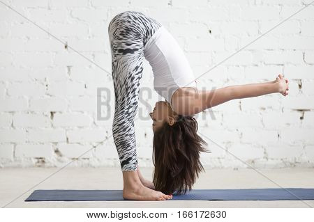 Young woman practicing yoga, standing in variation of head to knees exercise, uttanasana pose with hands behind back, working out wearing sportswear, indoor full length, white loft studio background