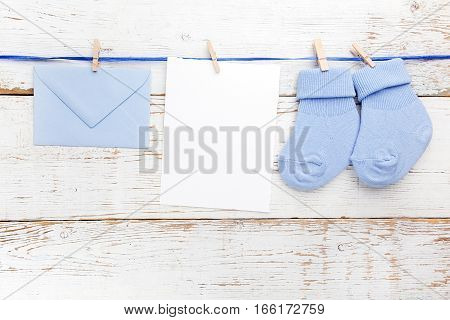 Small boy blue socks, blank card and evelop on white wooden background.