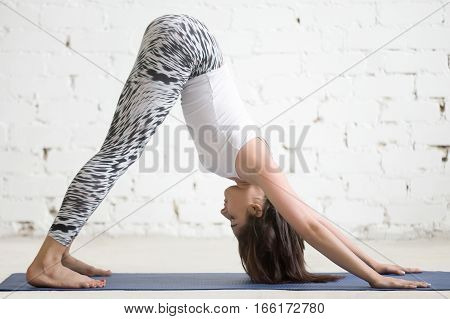 Young attractive woman practicing yoga, stretching in Downward facing dog exercise, adho mukha svanasana pose, working out wearing sportswear, indoor full length, white loft studio background