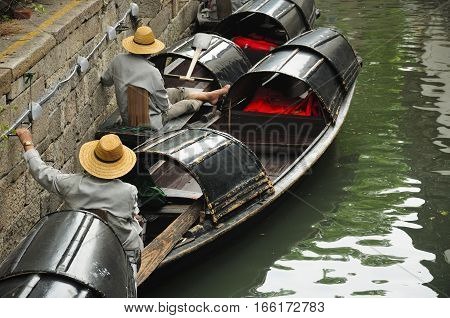 Chinese oarsmen sitting in the wu peng chuan or the black canopied boats on the canals of Lu Xun native place in the city of Shaoxing China in Zhejiang province.
