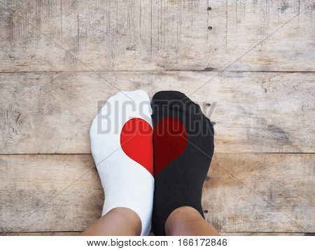 Selfie feet wearing white and black socks with red heart shape on wooden floor background. Love concept.