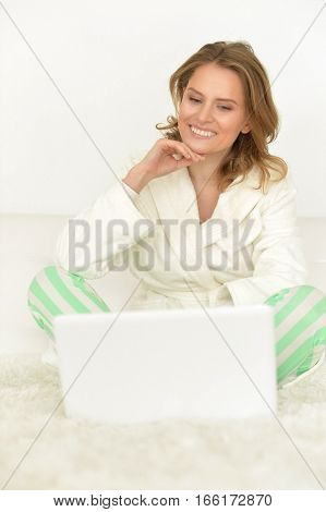 Happy young woman with laptop sitting on bed
