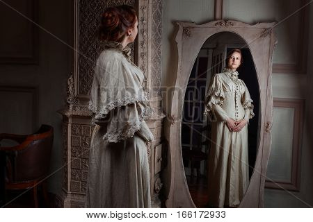 Woman in retro style noblewoman standing in front of the mirror trying on a dress.