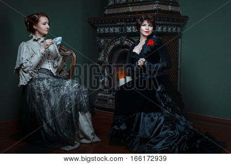 Retro woman drinking tea near the fireplace and lead the conversation they are dressed in lavish dresses.