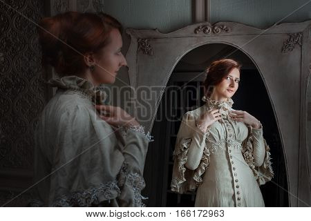 Woman in front of a mirror does the toilet is trying on a dress in a retro style.