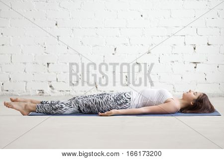 Young attractive woman practicing yoga, lying in Dead Body, Savasana exercise, Corpse pose, working out wearing sportswear, top and pants, indoor full length, white loft studio background