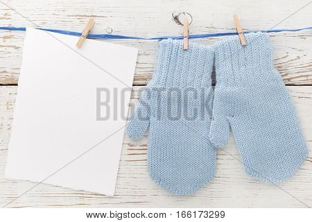 Small baby gloves, blank card on white wooden background.