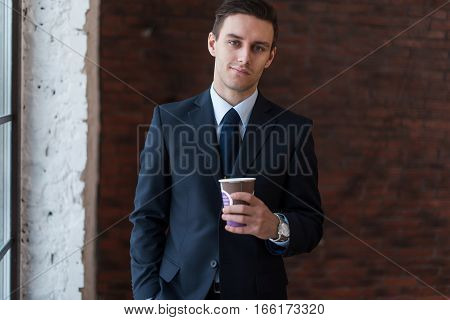 Businessman drinking coffee in office standing near window looking at camera
