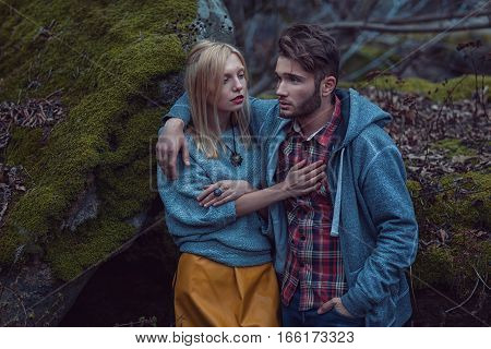 The guy put his arm around girl she was cold in the autumn.