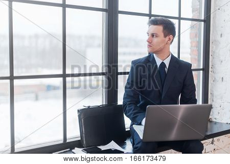 Businessman working on his laptop computer sitting in office.