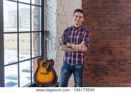 Handsome casual style man with guitar smiling and looking at camera