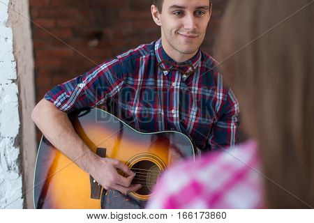 Young man singing playing guitar for his girlfriend.