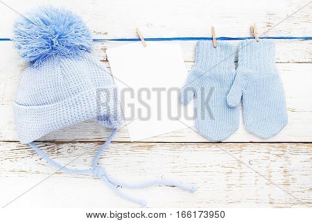 Small baby gloves, cap blank card on white wooden background.