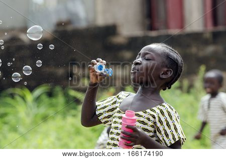 African Girl Playing with Soap Bubbles Outdoors in Bamako Mali. Black young beautiful girl having fun outdoors blowing soap bubbles. Happiness symbol. Elementary student happy outside her school.