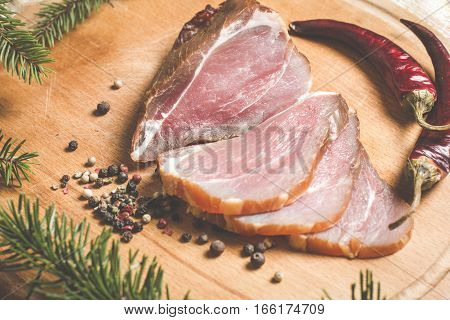 smoked ham with pepper on a wooden board decorated with fir