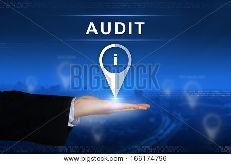 audit button with business hand on blurred background