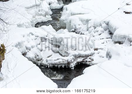 River incased in snow and ice with animal tracks.