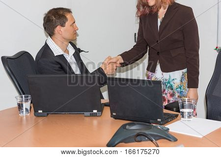 Young business woman and man shaking hands at table and smiling