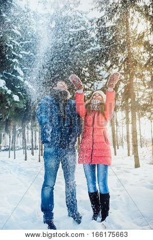 woman and man having fun in winter forest