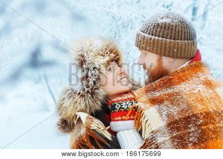 Happy romantic smiling lovers hugging on snowy winter outdoor. Winter love story. Valentine's Day, people, season, leisure and love concept. Young family couple covered with plaid blanket in forest