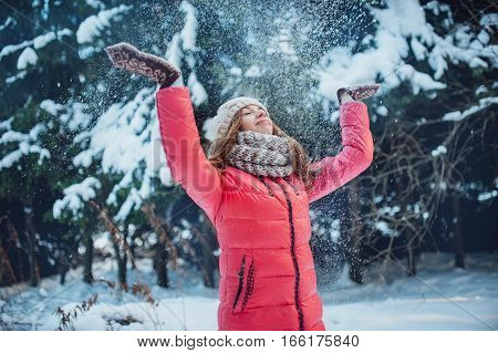 beautiful girl throws up snow in the forest