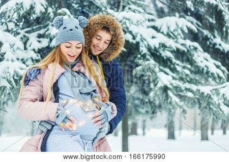 Young pregnant couple in winter forest. Expectant mother and her husband waiting for baby in winter. Love, family, pregnancy concept. Happy family. Future mom with husband holding pregnant belly