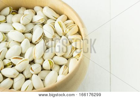 White cooked Pistachio snack in wooden bowl