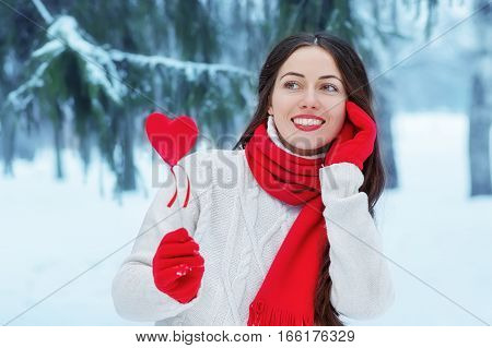 Girl in winter forest holding a heart in hands. Valentine's day concept. Winter outdoor portrait of positive young woman in sweater, red glove and scarf with red heart decoration in hands