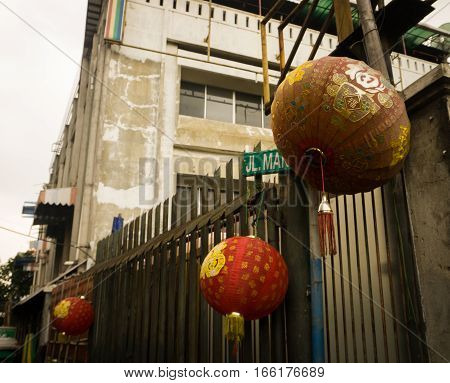Red lanterns hang on fence in front of a house photo taken in Jakarta Indonesia java