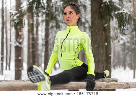 Fit woman athlete doing left leg split stretching exercises outdoors in woods. Female sports model exercising outdoor winter park.