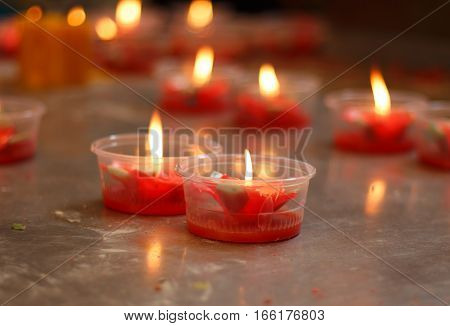 Burning red flower candle at chinese shrine for making merit in chinese new year festival.