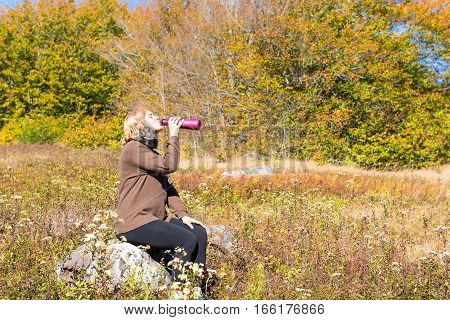 Young woman sitting on rock in meadow drinking water from bottle during hike