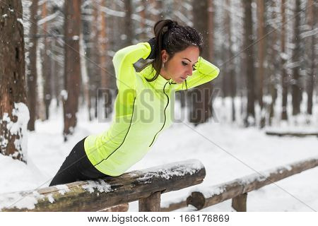 Fit woman doing back extension exercise outdoors in woods. Female sports model exercising outdoor winter park.