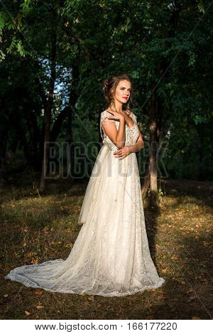 Beautiful bride in a wedding dress standing in the park, autumn time