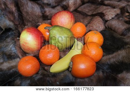 bight colorful juicy fruits lay on fur red  apples, green pear, persimmon, ripe banana and sweet mandarine