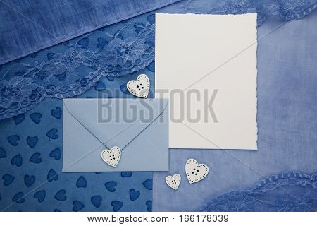 composition of the empty cardboard card and an envelope on fabric background
