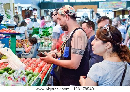 Montreal, Canada - July 26, 2014: People buying produce at Jean-Talon farmers market in downtown with fruit displays
