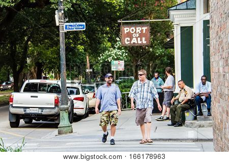 New Orleans, USA - July 13, 2015: People walking on historic Dauphine district during daytime with port of call sign