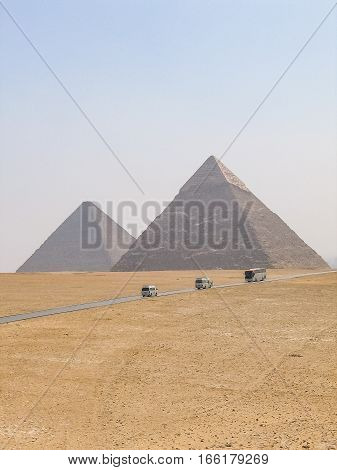Many tour buses and cars driving on road through great pyramids