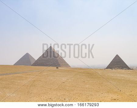 Three pyramids in Giza with road landscape