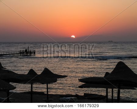 Red sunset at Egyptian beach with straw umbrellas and sea