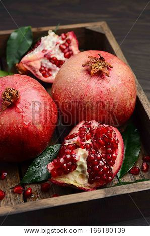 Fresh pomegranates on dark wooden background, selective focus