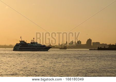 New York, USA - May 10, 2015: Hornblower Infinity passenger ship on Hudson Bay with cityscape at sunset