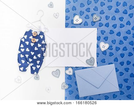 Blank card, envelop and overalls on paper background.