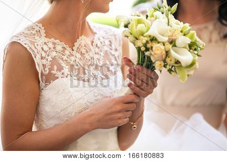 Delicate Bride Holds A Wedding Bouquet Of Callas And Roses