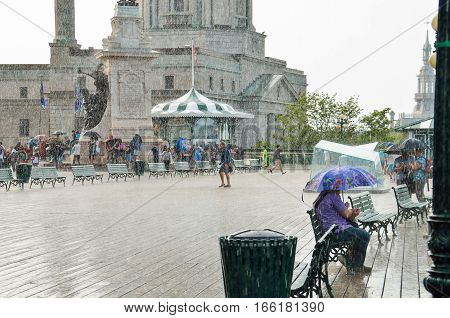 Quebec City, Canada - July 27, 2014: Crowd of people taking out umbrellas and walking in heavy rain on Dufferin terrace boardwalk street close to Chateau Frontenac.