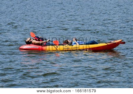 Washington DC, USA - April 12, 2015: People in tandem kayak resting and looking at phone on Potomac river