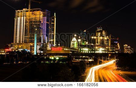 Austin, USA - July 19, 2015: Austin cityscape at night with Power Plant, Trader Joes, and road with neon lights